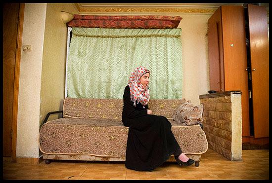 Jeune fille dom pose sur un canapé à Shu'fat