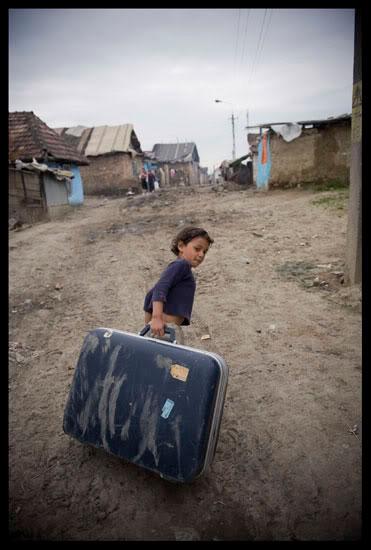 enfant rom jouant avec une valise