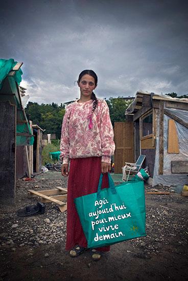 Jeune femme rom avec un sac Carrefour a la main